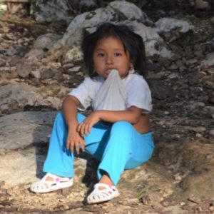 Small girl sitting on stone